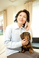 A Senior Adult Woman Holding a Dog and Talking on a Mobile Phone, Front View, Side View, Differential Focus