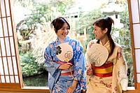 Two women in Yukata sitting and holding Japanese fans, front view, Japan