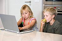 A brother and sister using a laptop