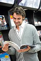 Man reading magazine in supermarket