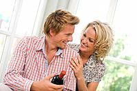 Young couple holding wine bottle, smiling, portrait