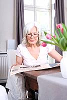 Senior woman reading newspaper, portrait