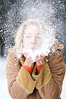 Austria, Salzburger Land, Altenmarkt, Young woman blowing snow off hand, portrait