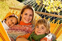 Austria, Salzburger Land, Altenmarkt, Mother and children lying in hammock, smiling, portrait