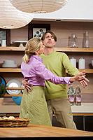 Young couple dancing in kitchen, portrait