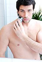 Young man man using electric razor, portrait