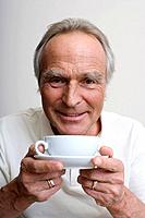 Senior man holding cup of coffee, portrait