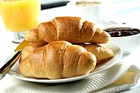 Coffee cup, orange juice, croissants, marmalade