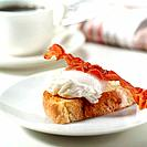 Poached egg on toasted bread with crispy bacon