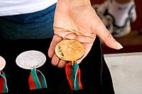 Volunteer holding gold medal in her hand, Special Olympics, U of M Bierman Athletic Complex, Minneapolis, Minnesota, USA