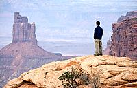 Hiker enjoys the view of Candlestick Tower in Canyonlands National Park, Moab, Utah, USA