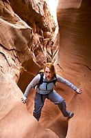 Female hiker scrambles through a narrow section of Little Wildhorse Slot Canyon in the San Rafael Swell, Utah, USA