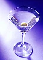 Martini cocktail with olive, purple background