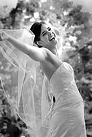 Bride with arms outstretched holding veil, outdoors