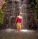 Young woman standing under waterfall