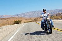 Man riding motorcycle on desert road