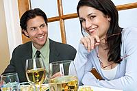 Mid adult couple at restaurant table woman looking at camera