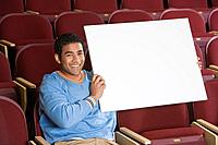 Man sitting in auditorium holding empty placard