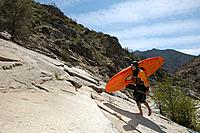 Female kayaker walking on rock side view