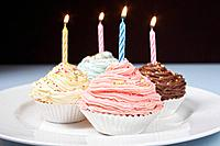 Pastel cupcakes with birthday candles on plate