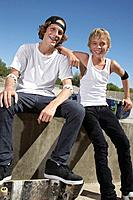Two teenage boys 16_17 with skateboards at skate park portrait