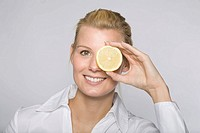 Woman with lemon slices in front of her eyes