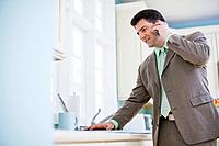 Businessman Using Cell Phone in Kitchen