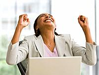 Hispanic businesswoman cheering next to laptop