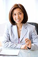 Asian businesswoman holding eyeglasses