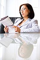 Asian businesswoman reading paperwork