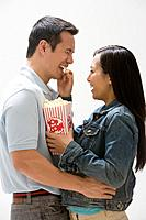 Asian woman feeding popcorn to boyfriend