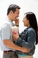 Asian woman feeding popcorn to boyfriend