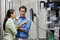 Multi_ethnic coworkers working in computer server room