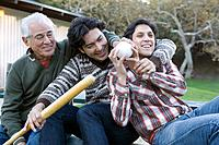 Hispanic grandfather and grandsons playing with baseball and bat