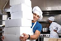 Hispanic male pastry chef carrying stack of boxes