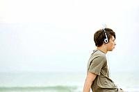 Teen boy sitting on beach listening to headphones, side view