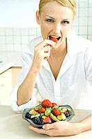 Woman holding bowl of fruit salad, eating strawberry, looking at camera