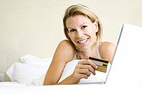 Woman lying in bed with laptop computer, holding credit card, smiling at camera