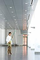 Man standing in lobby, playing air guitar with broom, listening to headphones, smiling at camera