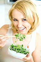 Woman eating radish sprouts with chopsticks, smiling at camera