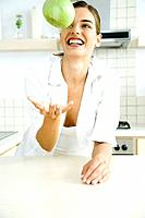Woman with toothy smile tossing an apple in the air, in kitchen