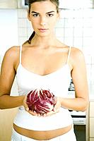 Young woman holding a head of radicchio lettuce in kitchen
