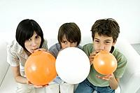 Mother and two sons inflating balloons, woman and one son looking at camera