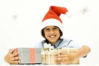 Boy holding stack of Christmas gifts, wearing Santa hat, smiling at camera