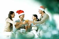 Two couples toasting and exchanging gifts, men wearing Santa hats