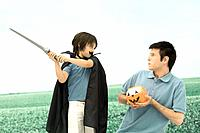 Father and son playing, man holding jack o' lantern, boy swinging sword