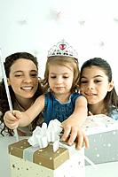 Girl dressed as princess, reaching for presents, mother and sister watching