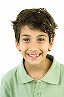 Boy with confetti in his hair, smiling, portrait