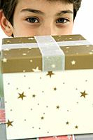 Boy looking over presents at camera, close-up