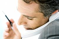 Man holding phone between chin and shoulder, side view, close-up (thumbnail)